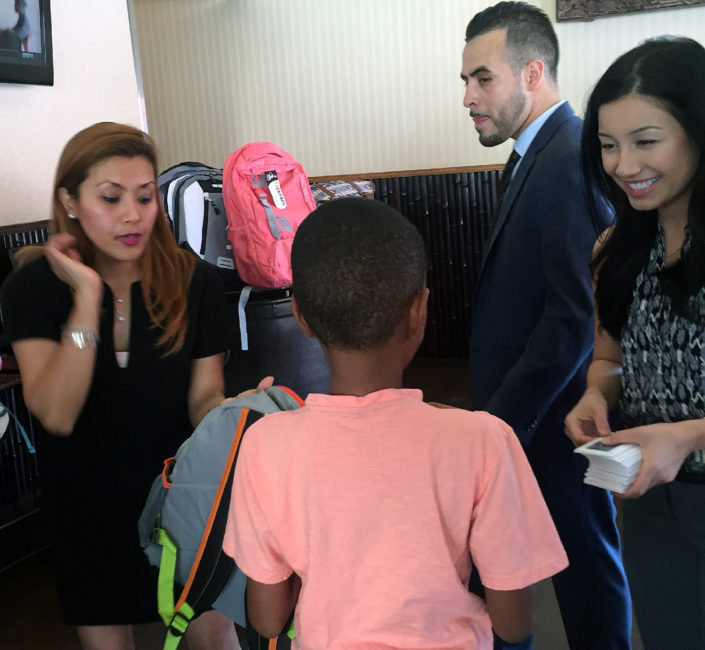 Chin Chin staff handing out backpacks and gift cards to foster youth