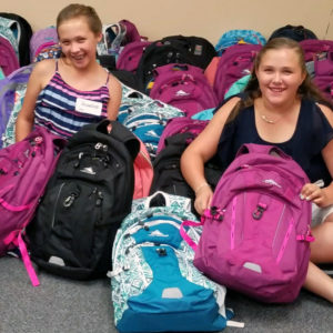 Crisafulli twins sitting amid donation of 100 backpacks