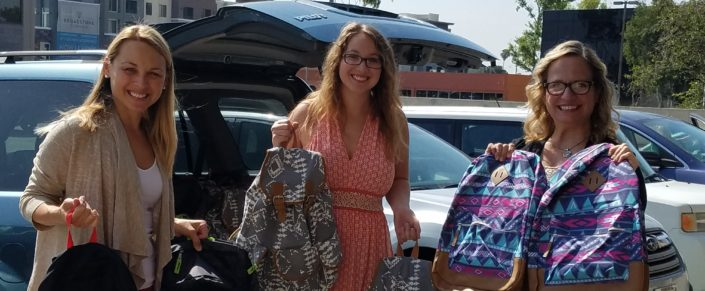 Global Algae staff delivering backpacks for foster children and youth
