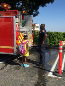 Little girl wearing her new backpack while talking with a firefighter about his firetruck
